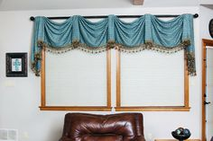 Bright and Innovative - Dazzling blue fabric is elegantly draped across the window to create a kingston valance style treatment. The signature embellishment and jewel trim add a touch of sophistication. The view is undeniably pleasing. - Brandi Renee Designs, LLC - www.brandireneedesigns.com