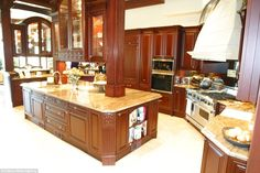 The kitchen is finished with a wooden effect but still appears to have modern comforts including several large ovens