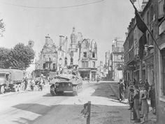 Normandy, 1944, push inland, the Falaise Gap: Residents of Avranches watch vehicles belonging to a US armored unit move through the street. Some of the destruction caused by the shelling of the town preceding its capture can be seen in the background.