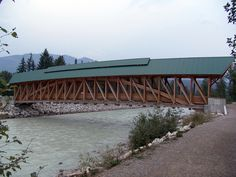 "Kicking Horse Pedestrian Bridge ~ Golden, BC, Canada • ""Kicking Horse Pedestrian Bridge is the longest freestanding timber frame bridge in Canada. Planned as a community project by the Timber Framers Guild, volunteers from Golden were joined by carpenters and timber framers from the United States and from Europe. The bridge structure is 150 feet (46 m) long, with a 210,000-pound Burr arch structure. The bridge was completed in September 2001.""j"