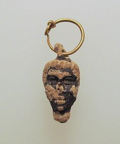 Gold hoop with glass pendant in the form of a youthful head with negroid features Period: Hellenistic Date: late 2nd–1st century B.C. Culture: Greek, Eastern Mediterranean Medium: Gold, glass; cast in a two-part mold.                               MET                ...