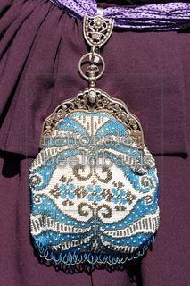 Antiek zilveren beugeltasje behorend bij Drentse klederdracht op heidekleur jurk
