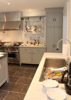 Inn at Little Pond - Gorgeous kitchen features gray cabinets accented with oil-rubbed bronze hardware paired with white marble countertop and ceiling height subway tile backsplash.