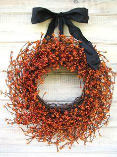 Corona de navidad con plantas o hierbas secas…  plantas con frutos rojos y se ha combinado con un gran lazo negro. Navideño y muy elegante.