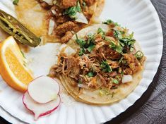 Carnitas, a Mexican-style pulled pork, gets tangy punch from the addition of spicy pickled jalapeño brine to the cooking liquid. The meat then gets piled high into warm taco shells.
