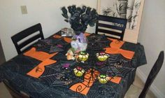 Halloween table decor. Centerpiece is a vase with spiderwebs, spiders and black roses.