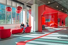 Cool, muted colors prevail over the space, with vibrant pockets of red throughout. Reflecting Comcast's origins as a cable provider, the design of the space takes cues from a two-dimensional electrical wiring diagram.