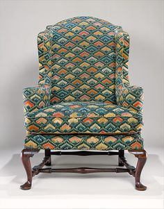 Eighteenth-century easy chairs—heavily  padded, with thick down-filled cushions, and with wings to rest one's head against and keep drafts away—were often reserved for the elderly or the infirm. This New England example is remarkable for its elaborate upholstery and intact condition