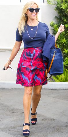 Reese Witherspoon's Sunniest Street Style Looks - August 15, 2017: Reese Witherspoon stepped out in Los Angeles on Tuesday wearing a navy tee, a magenta floral skirt from her own line, denim platform sandals, a monogrammed Parker Thatch tote and a pair of blue cat-eye sunnies .