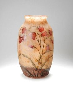 Vase, ca. 1905 ..      Highly attractive, triple cased Daum vase of oval form, H. 37,3 cm, with rose and peach-coloured powder as well as multicoloured oxyde inclusions, matte, acid-etched ground, relief decoration in the form of bell-flowered plants in rose, dark-red and green enamel colours, signed on the side DAUM NANCY FRANCE, with the Cross of Lorraine.
