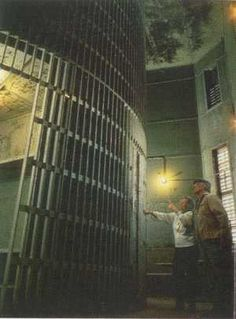 """Squirrel Cage, Old Pottawattamie County Jail, Iowa: The """"Squirrel Cage"""" Jail, in use from 1885 until 1969, is one of three remaining examples of a Rotary Jail. It has pie-shaped cells on a turntable. To access individual cells, the jailer turned a crank to rotate the cylinder until the desired cell lined up with a fixed opening on each floor. A former jail tour guide claimed she believed the ghost to be that of J.M. Carter, the man who oversaw the building's construction. Mr. Carter was the firs"""