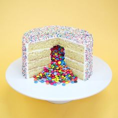"Crumbs and Doilies, London | Based near Oxford Circus, Crumbs and Doilies are known for their cupcakes, but their cakes are delicious too. Like this pinata cake aka ""4 layers of vanilla sponge filled with mini Smarties and covered in sprinkles."" Delicious.15 Places You Must Eat Cake Before You Die"