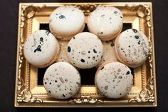 Dessert table & macaron decoration - French macaron cookies with gold and violet/navy/emerald paint splatter decoration on gold tray