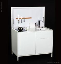 Kitchenette exclusive avec des façades en blanc laqué et un plan de travail en corian. L'évier en corian également en continuité du plan de travail fait la différence.