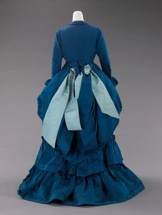 "Afternoon Dress, Charles Frederick Worth (French (born England), Bourne 1825–1895 Paris) for the House of Worth (French, 1858–1956): ca. 1872, French, silk. ""The full-blown bustle silhouette had its first Victorian appearance in the late 1860s, which started as fullness in skirts moving to the back of the dress. This fullness was drawn up in ties for walking that created a fashionable puff..."""
