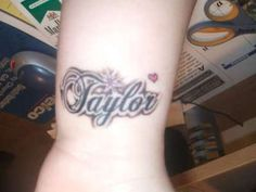 A free style name tattoo with a tiny cute red heart designs on girl's wrist.