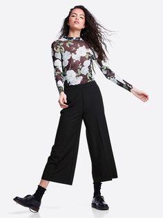 Bukser med høyt liv og vide rette ben med ankellengde. Buksene har sidelommer og en glidelås bak. Svart