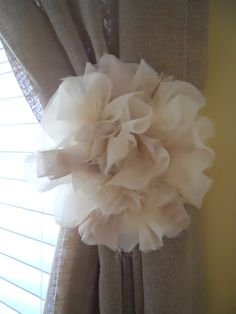 Flower Curtain Tie Backs. They use a hook on the wall to hold it there.