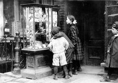 Kids checking out some comics and toys at a store around 1900.