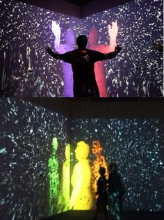 """""""Il dono della massa"""" is an installation located in the church of St. Nicholas in Modena, small and dark location, suited to purpose of recreating immediate aftermath of Big Bang;it consists of two large screens that show a dance of gray dots, under which there is a stage on which the visitor can go up and may notice a colored and indistinct figure; as the figure is modeled more and more and takes the form of the visitor's body,it reproduces the look and follows the movements. Year 2012"""