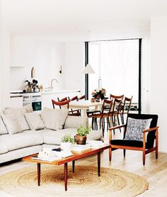 Open living room with a dinning space, a sectional, and a black leather chair