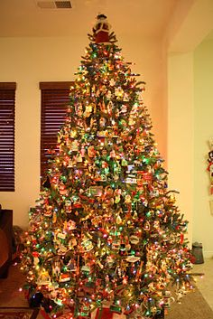 A Traditional Christmas Tree decorated with an abundance of smaller Character Ornaments!!! Bebe'!!! A Santa Claus Tree Topper sits a top  the tree!