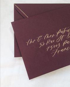 gold calligraphy on burgundy maroon envelope addressing • paulaleecalligraphy • paulaleecalligraphy.com