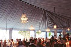 Hanging chandeliers in wedding tent