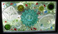 Recycled glass art{ Recycled bottle bottoms, glass beads, sanded glass pieces and decorative glass pieces glued with E600 craft glue onto an old single pane window. By Teena Stewart.