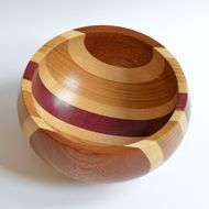 This unusual bowl has some beautiful natural coloured woods that compliment each other so well; made from Elm, Sapele, Maple and Purple Heart wood. Each segment of the bowl has been re-sawn to size, planed and then given a quick sanding before being gl...