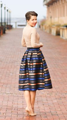 Smiling pale-skinned brunette in updo, blush ribbed sweater, copper/cobalt/bronze striped A-line skirt, nude stilettos; red brick boardwalk flanked by old cream masonry façade