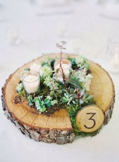 Wedding Flowers A rustic wedding centerpiece with moss, woodsy table number and succulents. - Designing your wedding centerpieces can be tough. Here's some of our favorite table focal points for your celebration. Votive Centerpieces, Succulent Centerpieces, Rustic Wedding Centerpieces, Wedding Decorations, Table Decorations, Centerpiece Ideas, Centerpiece Flowers, Succulent Arrangements, Rustic Candles