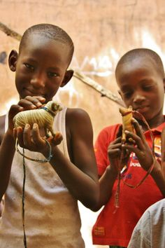 Cute little boys showing off their prized wooden todays in Bamako, Mali. Photo credit: Julienne Oyler.