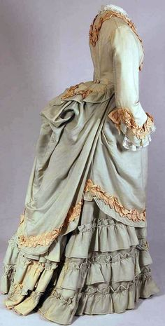 Two-piece day dress, Nice, France, ca. 1870-75. Light green cotton/wool with beige pleated silk trim. Bodice lined with cotton, closes with fabric-covered buttons. Skirt with pleats in back, hem reinforced with cotton and woolen band, closes with hooks & eyes at waist. Mode Museum, Antwerp
