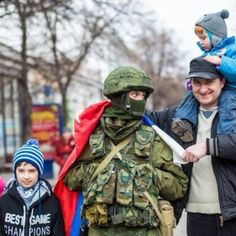 Crimean family takes a picture with a Russian soldier.