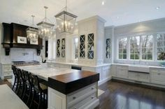 Love the white and dark brown contrast, butcher block next to the Carrara & glass cabinets