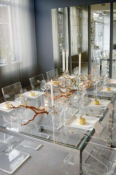 Natural branches and candlesticks line the center of this lucite table for a modern take on Thanksgiving.