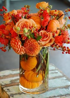 fall arrangement with pumpkins, dahlias, roses & berries.