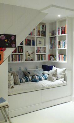 Cuarto de lectura con un sofá que esta bajo las escaleras
