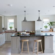 Take a modern approach to decorating a country kitchen with a grey and white palette commonly found in Scandinavian decor. Natural materials, such as the granite and wood worktops, tie in perfectly with this Nordic take on the scheme. This kitchen has nothing superfluous about it, and is meticulously planned to ensure easy access to cabinets and plenty of space to move around the island.