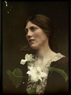 Portret van een vrouw gekleed in een rode jurk met twee witte bloemen voor haar borst, anoniem, 1907 - 1930