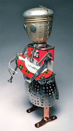 I call this kilted character Tiny MacNutmeg  Its a scott-ish sculpture I made from recycled materials including:  • AG nutmeg spice tin • vegetable steamer parts • tea infuser • scotch tape tin • toy forks  Any fan of vintage spice tins will have a highland fling for this punny fellow. But dont expect any tinny tunes (hes a sculpture not a working bagpiper, after all).  10 x 9 x 12  I started by looking for interesting vintage kitchen pieces to make my kitschy robots. I fastened them…