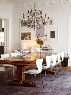 Piet Hein Eek's table, made ​​from waste wood, specially ordered from NK. Around the table are ten Seven Chairs by Arne Jacobsen. The large antique carpet from Knut is bleached and colored in gray. Ceiling light units in 2097, designed by Gino Sarfatti for Flos.