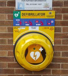 Nottinghamshire, United Kingdom (UK) unlocked AED Cabinet - Automated External Defibrillator in yellow color with AED logo and backboard information. The cabinet must also present the international ICLOR defibrillator symbol on the front and standing out from the background colour of the cabinet. Wall signage to support the location is advisable.