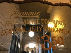"A photo of a mirrored sign inside of the Doughnut Vault shop in Chicago, Illinois that says, ""Famous Half Calorie Doughnut Seasonal Jelly Doughnut $3.50."" Learn more about this tiny ""hole"" in the wall donut shop by reading the FoodWaterShoes article, ""They're Coming to Take Me Away, Ha Ha! – Doughnut Vault in Chicago, Illinois"" - Food Foodie Foodies FoodPorn Snacks Food Shop Eat Restaurants Local Eats Eating Fried Food Breakfast Brekkie Brunch"