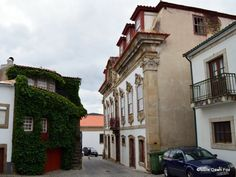Ornate 18th century manor house opposite ivy-covered cottage, Provesende, Douro Valley, Portugal