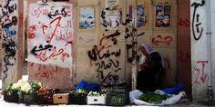 Una mujer vende verduras en Dheisheh.