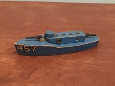 Vintage wooden toy navy gun boat. Measures about 5.5 long, 1.5 wide, and 1.25 tall. Condition is as seen in photos. Scratches, missing paint, and other vintage wear as seen in photos. I think it is missing 4 small smoke stacks in the 4 empty holes on top. Please take a look and feel free to ask any questions. Thanks