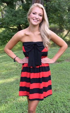 Turn heads at the tailgate this gameday season with this eye-catching red and black striped mini tube dress! The fun bow detail and bright colors of your Georgia dawgs or your favorite team will have you cheering UGA loud and proud. The comfy fabric and tube cut go great with boots and our matching bracelets.