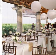 Liz and Zack's reception took place on the back patio of the Wolffer Estate, which was strewn with large, white paper lanterns. The tables were set with ivory linens and burlap runners to create an elegant outdoor setting.
